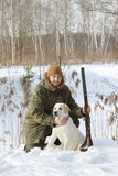 与拉布拉多猎犬和猎枪的猎人在冬天森林里 免版税库存图片