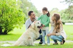 与拉布拉多猎犬狗的愉快的家庭在公园 免版税图库摄影