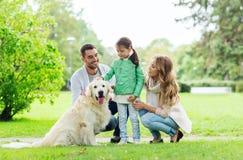 与拉布拉多猎犬狗的愉快的家庭在公园 免版税库存图片