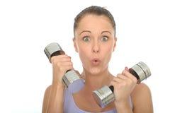 与拉扯傻的表情的沉默寡言的响铃重量的健康适合少妇训练 库存图片