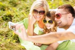 与拍照片的照相机的愉快的家庭 库存图片