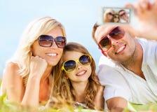 与拍照片的照相机的愉快的家庭 免版税图库摄影