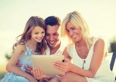 与拍照片的片剂个人计算机的愉快的家庭 免版税库存图片
