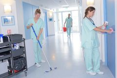 与拖把和制服清洁医院走廊的擦净剂 库存照片