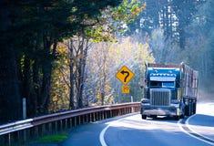 与拖车的蓝色半经典之作卡车船具在晴朗的有风路 库存图片