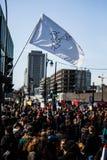 与招贴、旗子和标志的人群走在街道的 库存图片