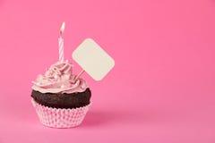 与招贴的桃红色生日杯形蛋糕 库存图片