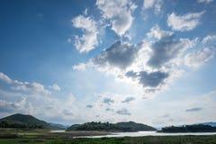 与拦截在他们后的太阳的多云的蓝天 库存照片