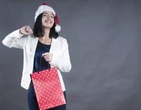 与括号的女孩秀丽盖帽圣诞老人礼物袋子 库存图片