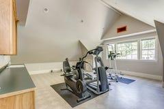 与拱顶式顶棚的设备完善的家庭健身房 免版税库存照片