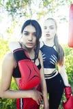 与拳击战斗的两个不同的国家女孩外面在绿色公园,体育夏天人概念 免版税库存图片