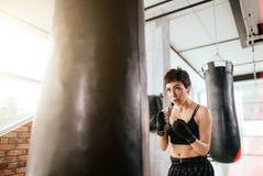 与拳击袋子的Kung fu女孩实践的空手道在体育馆 库存图片