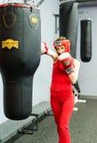 与拳击手套的少妇训练在健身房 图库摄影