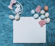 与拷贝空间的复活节卡片您的文本的 一个空插件、鸡蛋和兔宝宝 背景看板卡祝贺邀请 库存图片