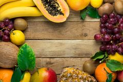 与拷贝空间的框架从新鲜热带和夏天结果实菠萝番木瓜芒果椰子桔子猕猴桃香蕉柠檬葡萄柚 免版税库存照片
