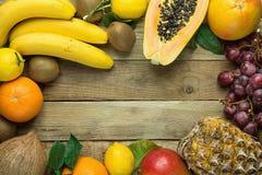 与拷贝空间的框架从新鲜的热带和夏天季节性果子菠萝番木瓜芒果椰子桔子猕猴桃香蕉柠檬 免版税图库摄影
