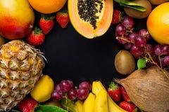 与拷贝空间的框架从新鲜的热带和夏天季节性果子菠萝番木瓜芒果椰子桔子猕猴桃香蕉柠檬 库存图片
