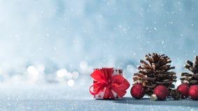 与拷贝空间的美好的简单的圣诞节背景 逗人喜爱的圣诞礼物、红色装饰品和杉木锥体在发光的背景 免版税库存照片