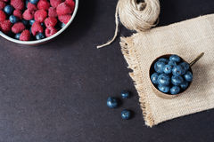 与拷贝空间的新莓和蓝莓黑暗的图片在左边 新鲜水果,在一个老铜杯子的莓果,碗 黑暗的猪圈 免版税图库摄影