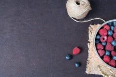 与拷贝空间的新莓和蓝莓黑暗的图片在左边 新鲜水果,在一个老铜杯子的莓果,碗 黑暗的猪圈 免版税库存照片