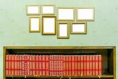 与拷贝空间的许多空的金黄木制框架在绿色贴墙纸了墙壁 书架,书 免版税库存照片