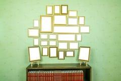 与拷贝空间的许多空的金黄木制框架在绿色贴墙纸了墙壁 登记书架 免版税库存图片