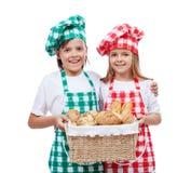 与拿着与面包店产品的厨师帽子的愉快的孩子篮子 免版税库存照片