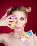 与拿着五颜六色的蛋白杏仁饼干,在红色背景的演播室射击的构成和创造性的发型的美好的模型 免版税图库摄影