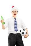 与拿着啤酒瓶和球的圣诞老人帽子的微笑的男性 免版税库存照片