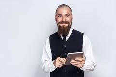与拿着数字式片剂和看与兴高采烈的面孔的胡子和把手髭的英俊的商人照相机 库存图片