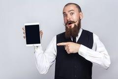 与拿着数字式片剂和看照相机和显示有手指的胡子和把手髭的英俊的商人屏幕 库存图片