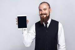 与拿着数字式片剂和看照相机和显示有面带笑容的胡子和把手髭的英俊的商人屏幕 免版税库存图片