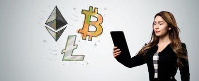 与拿着片剂计算机的妇女的Bitcoin Ethereum和Litecoin 图库摄影