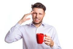 与拿着红色杯的头疼的英俊的商人 免版税库存图片