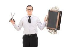 与拿着袋子的裁减领带的商人有很多金钱 免版税库存照片