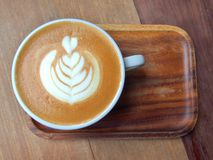 与拿铁艺术的平的加奶咖啡在木茶碟 免版税库存图片