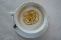 与拿铁艺术的Caffe拿铁在乳状泡沫层数的玫瑰色花纹花样在白色茶杯在白色织地不很细桌布 免版税库存照片