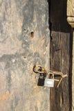 与挂锁的老被风化的生锈的门 图库摄影