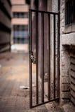 与挂锁立场的一个金属门道入口在一条肮脏的巷道打开 Jo 库存图片
