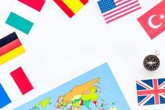 与指南针、旗子和地图的飞行的旅行在文本的白色背景顶视图空间 免版税库存图片