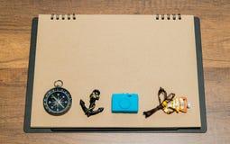与指南针、船锚、蓝色照相机和鱼项链的空白的包装纸在上面 免版税库存照片