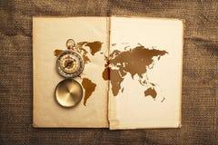 与指南针和世界地图的老开放书 库存图片