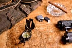 与指南针和双筒望远镜的老地图 图库摄影