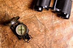 与指南针和双筒望远镜的老地图 库存图片