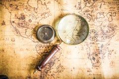 与指南针和放大器的老地图 库存照片