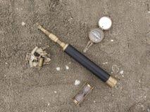 与指南针和望远镜的原始的背景在沙子 免版税库存照片