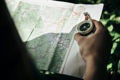 与指南针的旅客探索的地图在登上的晴朗的森林里 免版税库存照片