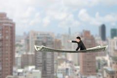 与指向手指姿态的商人坐金钱飞行 免版税库存图片