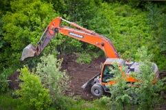 与挖掘机的清洁草丛 图库摄影