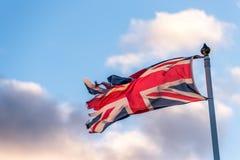 与挥动在多云天空的被撕毁的边缘的英国旗子 免版税库存图片